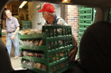 L to R: George Drotar (cq) watches volunteer Joe Duran (cq) unload food at the food bank of the...