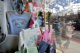 A pair of tourists walk past t-shirts on display in the window of the Estes Park Sweatshirt Center...
