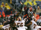 Denver Broncos defensive field goal team runs over the Washington Redskins line to block a 38 yard...