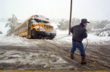 Castle Rock resident Brian Boyle (cq) helps a tow truck driver pull a bus whick skidded off Lake...
