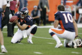 Denver Broncos quarterback Jake Plummer takes some snaps from center as the holder during field...