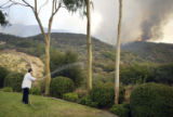 (NYT15) OAK PARK, Calif. -- Sept. 29, 2005 -- CALIF-FIRES-4 -- A man uses a garden hose to keep...