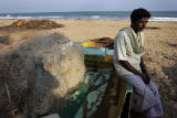 (1/17/05,Kaalapet, India)   Kuppurasu sits on his damaged boat and ponders his future in...