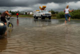 Broomfield, Colo., photo taken July 23, 2004-Tiffany Han,17, (right) skips across high water as...