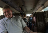 (1/18/05, Singarathoppu , India)   Rick Kitchens has a laugh with Scott Tidwell on the bus ride...
