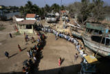 (1/18/05, Singarathoppu , India)   People wait in line to get food and cooking utensils in...