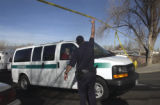 Aurora, Colo.-January 19,2005- An Aurora Police Officer lifts up the crime scene tape to let the...