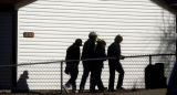 Aurora, Colo.-January 19,2005- Aurora Police investigators walk past the scene of a double...