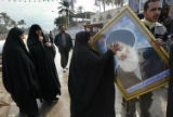 NYT4 - (NYT4) BAGHDAD -- Feb. 4, 2005 -- IRAQ-2 -- A woman touches a portrait of Grand Ayatollah...