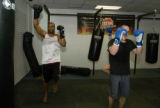 Michael Westbrook, left, works alongside Mike Macalister of Phoenix doing arm exercises between...