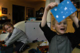 Scott Adams, 6, right shows off his Christmas card design while playing with his brother Nick, 8...