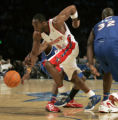 (DENVER, COLO.,  FEBRUARY 20, 2005) West's Kobe Bryant, center, blows past East's Dwayne Wade,...