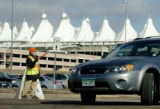 Denver, CO 02/03/05 RECORD NUMBERS FOR DIA Parking lot attendent Paul Carter directs cars to the...