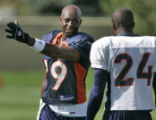 Denver Broncos' wide receiver, 19, Jerry Rice, left, talks with cornerback, 24, Champ Bailey,...