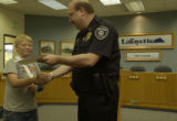 Ryan receives the proclaimation from Police Chief Schultz. Ryan Sullivan, (cq), 12, was awarded an...
