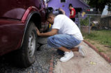 (DENVER, Colo., Aug 23, 2005) Danny Lopez,(cq) finishes changing the rear tire, that was flattened...