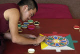 Lopen Kezang Dorjee, a Buddhist monk,  works on artwork made of different colored sand at the...