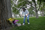 Mickey Garduno (cq) of Montrose places some flowers beside a tree in Buckley Park at the site of a...