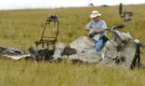 An Investigator looks over the wreckage of a twin-engine Cessna Sunday morning August 14, 2005...