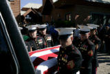 Marines carry the casket of Lance Corporal Evenor Herrera to a hearse that will take him to his...