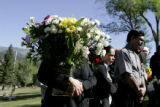 Mourners carry flowers for Marine Lance Corporal Evenor Herrera's funeral at Sunset View Cemetery...