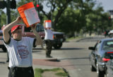 Ryan Dennis, 23, of the Guardian Angels holds a bucket he is using to take donations along Speer...