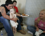 Relatives of Angela Coonce, cq, Mike Perkins, 20, of Pamperville, Mississippi, gives his 1-yr-old...
