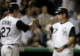 Garrett Atkins, left, and Todd Helton, right, bump fists after they both scored on a 3-run homer...