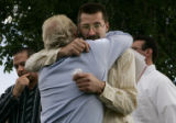 Tom Koldeway (cq) center, facing camera with glasses, hugs his lawyer Jeff Anderson(cq) , back to...