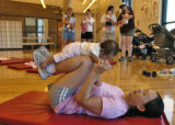 Sunah Cha (cq) works out with her baby Emily in Westminster City Park Fitness Center August 24,...
