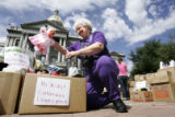 Dorothy Ciszek (cq), of Evergreen, puts a doll into a box at a rally at the State Capitol for...