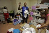 Hurricane Katrina evacuee Mack Murphy (cq, center), 58, of New Orleans waves thanks to the...