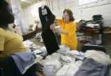 Adventist Disaster Response volunteer Ginger Vinland (cq, center), 69, of Lakewood offers up a...
