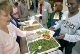 Volunteers of America employee Pat Stoehr (cq, far left) of Westminster serves a hot lunch to...