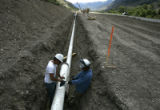 Two unidentifed workers install a 10 inch natural gas pipe line along Hwy 215 above Parachute ,...