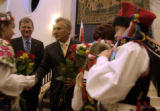 President Aleksander  Kwasniewski of Poland is presented flowers by members of Krakowiacy, a...