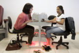 Katherine Bicker, cq, left, inspects Delliccia Honore's, cq, manicure while their pedicures dry at...