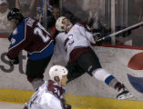 Jason Krog slams Jason Lynch against the boards in the third period of the Colorado Avalanche...