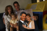Recently married couple, William Rimbey (cq),34, holds up a studio wedding picture with his wife...