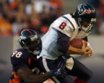 Houston Texans quarterback David Carr, right, is sacked for a three yard loss by Denver Broncos...