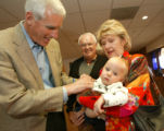 Pete Coors, left, greets Rocco Lowrey and his grandparents, Mimi and Tom, after services at St....