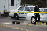 Denver, Co.,  October 28, 2004.  Evidence markers and a stray tire lay scattered on 26th Ave....