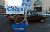 (DENVER, CO., OCTOBER 29, 2004)  A Ken Salazar supporter waves a sign at a truck with a Pete Coors...