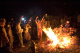 (BOULDER, October 30, 2004)  Crowd members cheer as a person throws a branch onto a fire created...