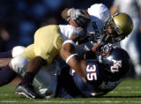 Colorado's Stephone Robinson (1) is pulled down by Kansas' Brandon McAnderson (35) in the second...