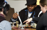 (DENVER, CO. NOVEMBER 18, 2004) Carmelo Anthony looks for a good place to autograph Maria...
