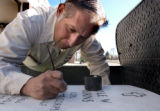 (Denver, Colo., November 19, 2004) Andrew Alonzo touches up the lettering on the headstone of...