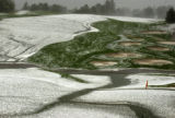 (Castle Rock, Colo., August 3, 2004) Hail covers the green at the 18th hole after a storm dumped...