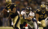 New Orleans Saints quarterback Aaron Brooks, left, flees the pressure of Denver Broncos defensive...