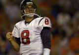 Houston Texans quarterback David Carr looks at the scoreboard and flexes his hand after hitting it...